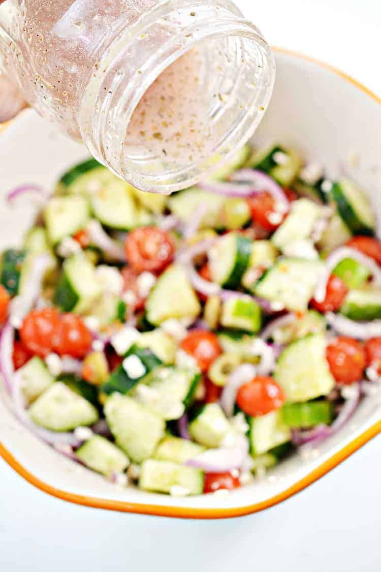 greek salad dressing being poured into keto greek salad in a bowl