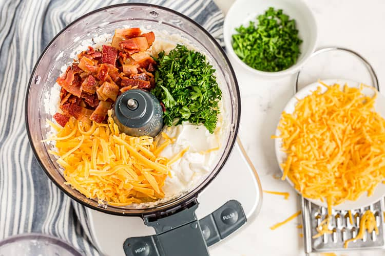 overhead view of food processor with cheese, bacon, and parsley