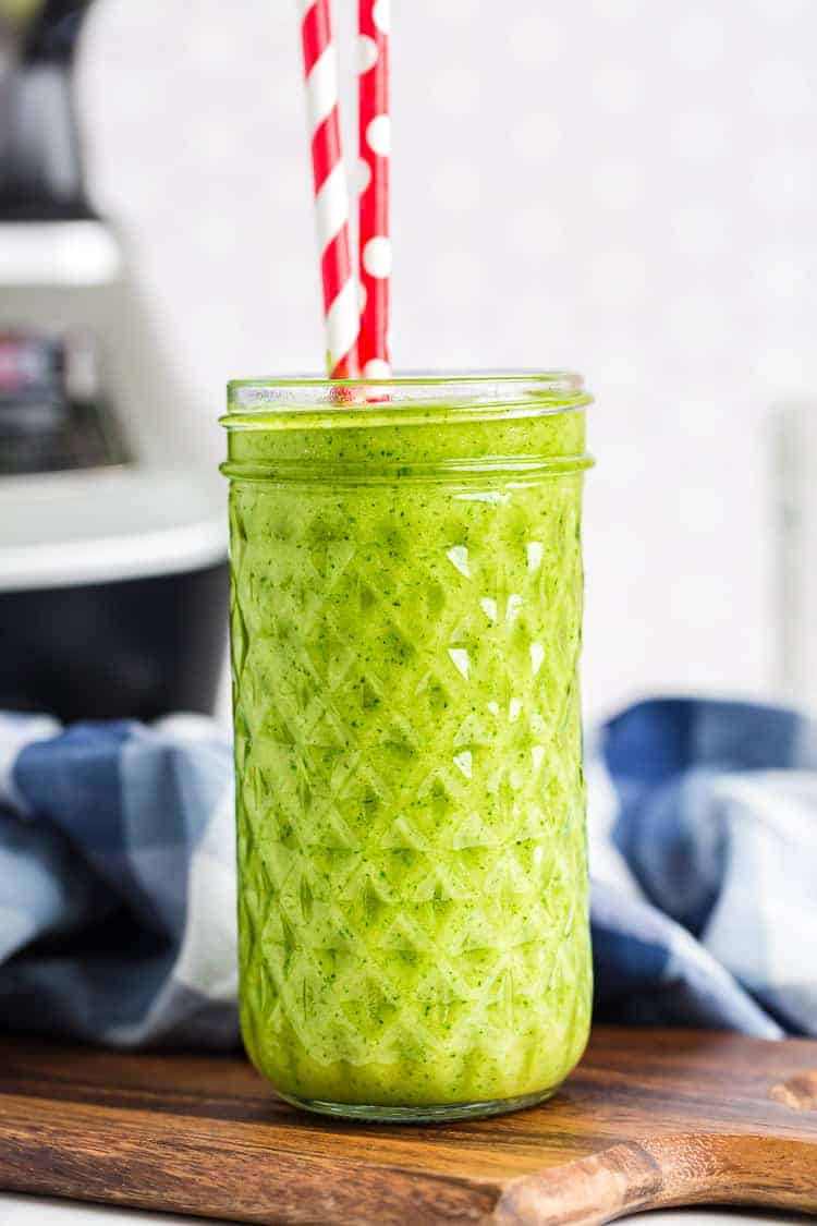 Vanilla Ice Cream Keto Green Smoothie in a tall glass with two red and white straws