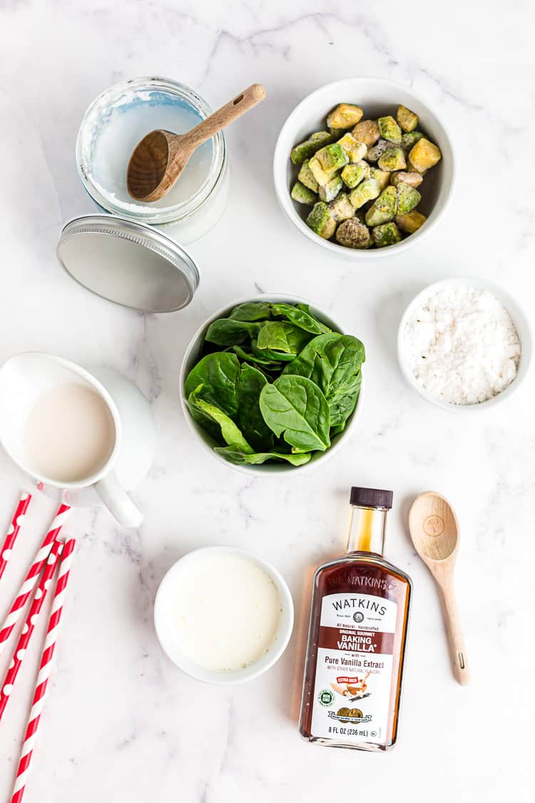 overhead view of smoothie ingredients such as spinach, vanilla extract, and avocado