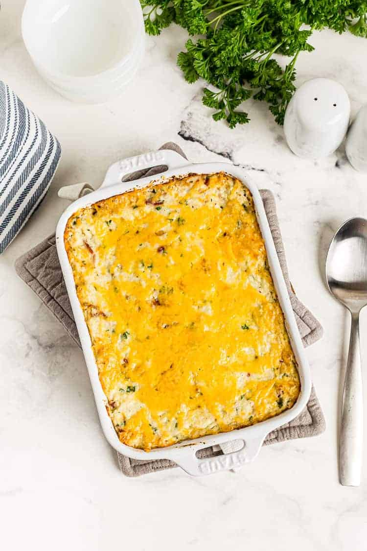 overhead view of fully baked cauliflower cheese casserole keto dish next to parsley