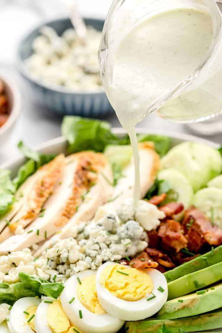 dressing being poured onto healthy cobb salad