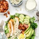 overhead view of keto cobb salad next to bowls of bacon, cheese, and dressing