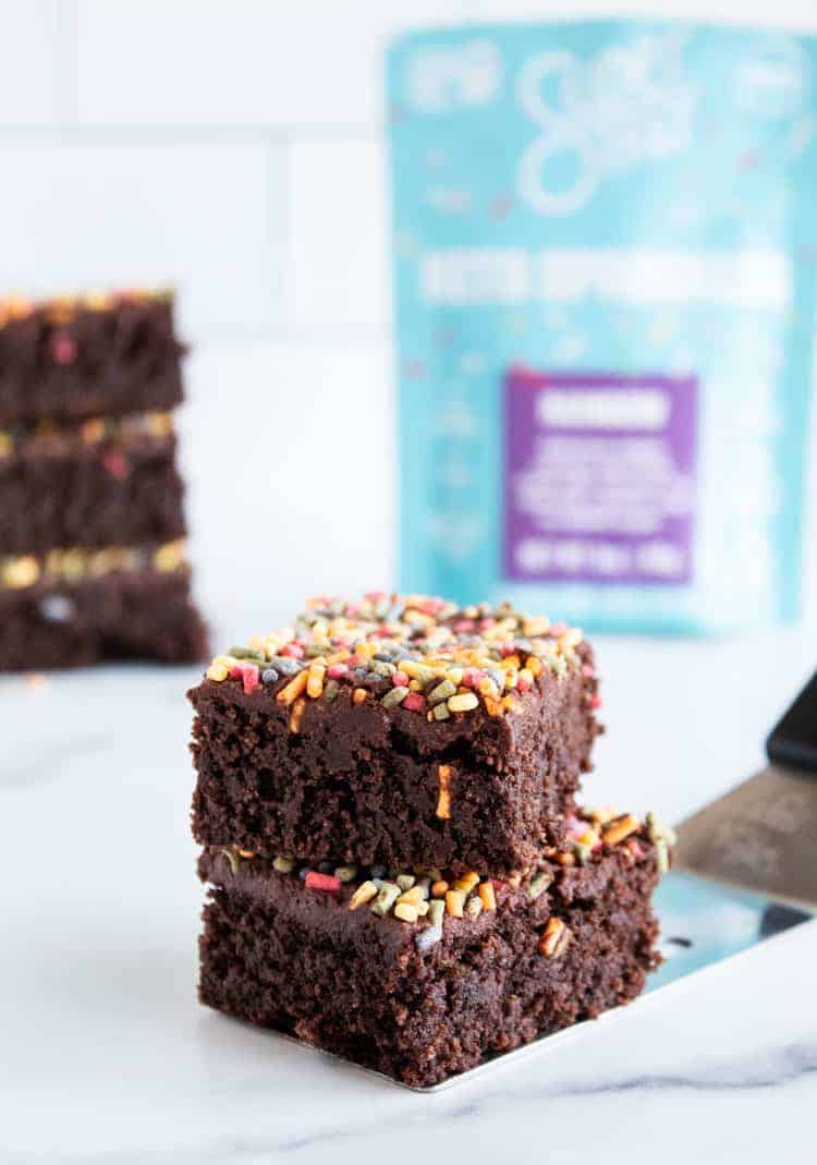 two keto brownies stacked in front of a bag of keto sprinkles