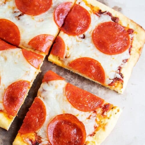overhead view of slices of keto pepperoni pizza on pizza stone