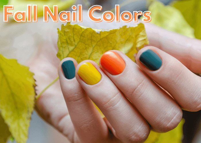 hand with fall nail colors holding a leaf