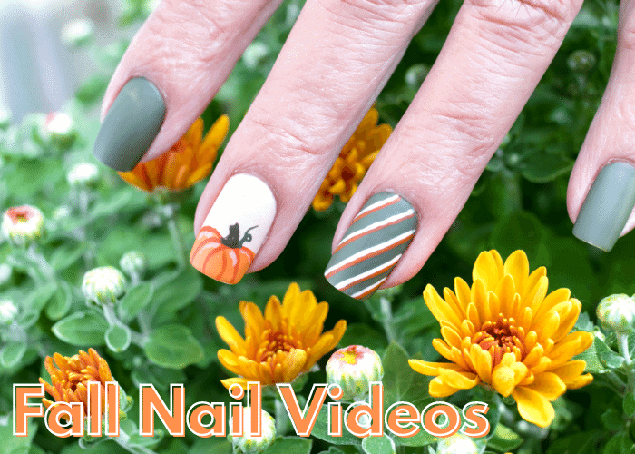 hand with various fall nail ideas on top of flowers