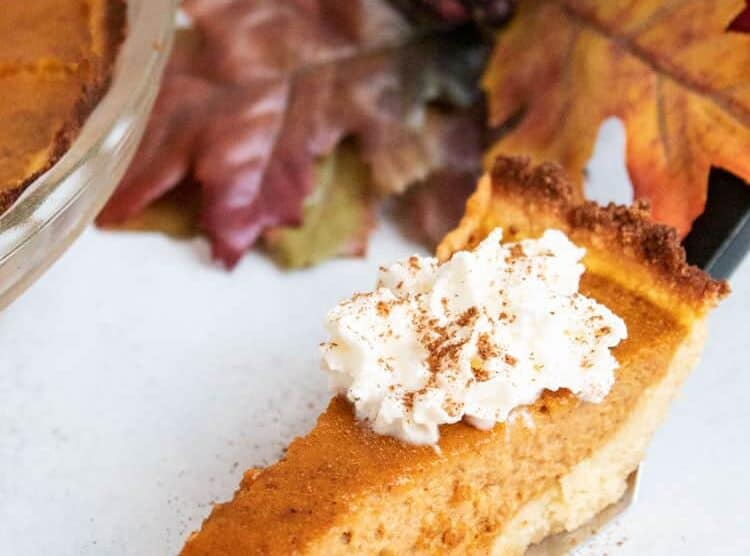 slice of keto pumpkin pie with whipped cream on top next to pie dish